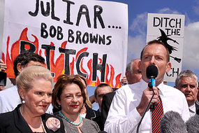 Abbott fronting the 'No Carbon Tax' rally, backed by abusive signs
